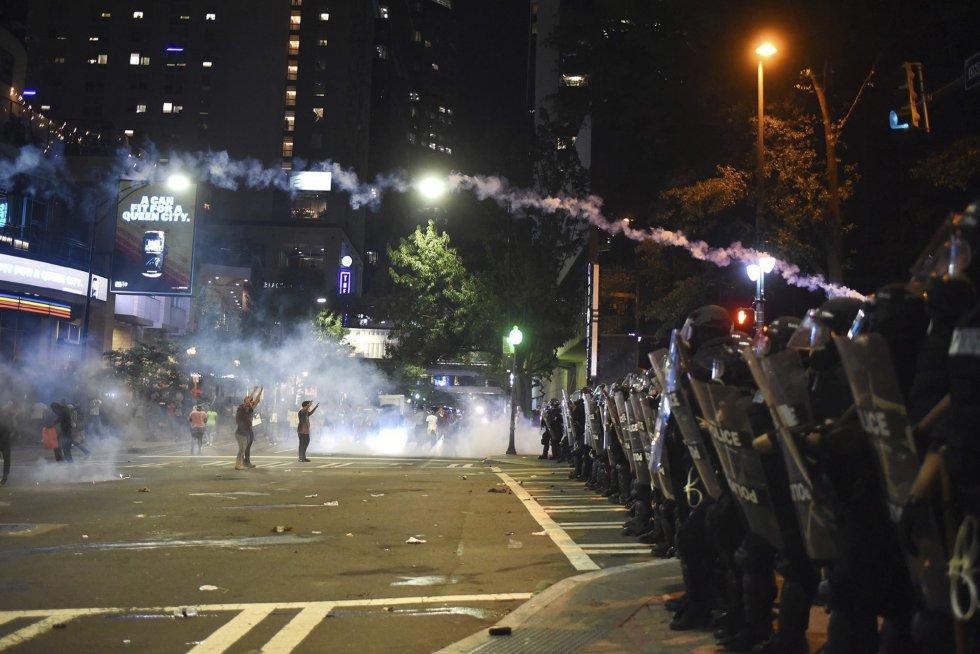 Dos manifestantes se encaran a policías antidisturbios con los brazos en alto durante unos disturbios en Charlotte en Carolina del Norte (Estados Unidos).