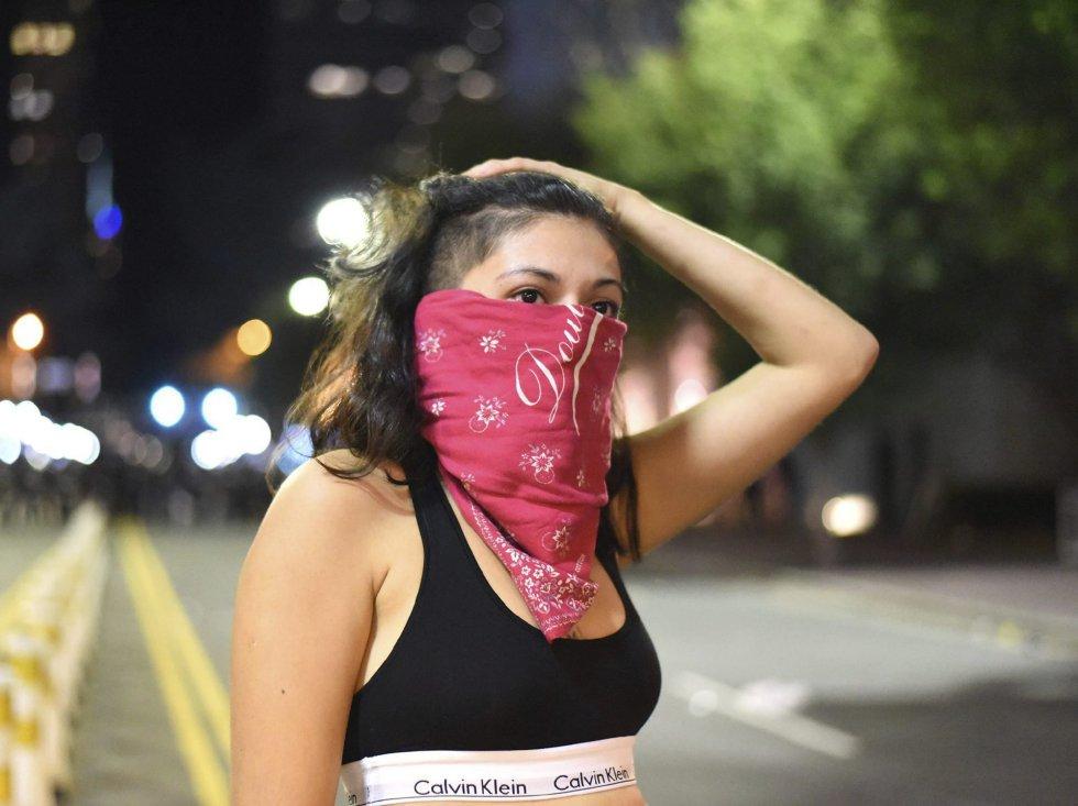 Una manifestante se cubre el rostro durante unos disturbios con la policía antidisturbios en Charlotte en Carolina del Norte (Estados Unidos).