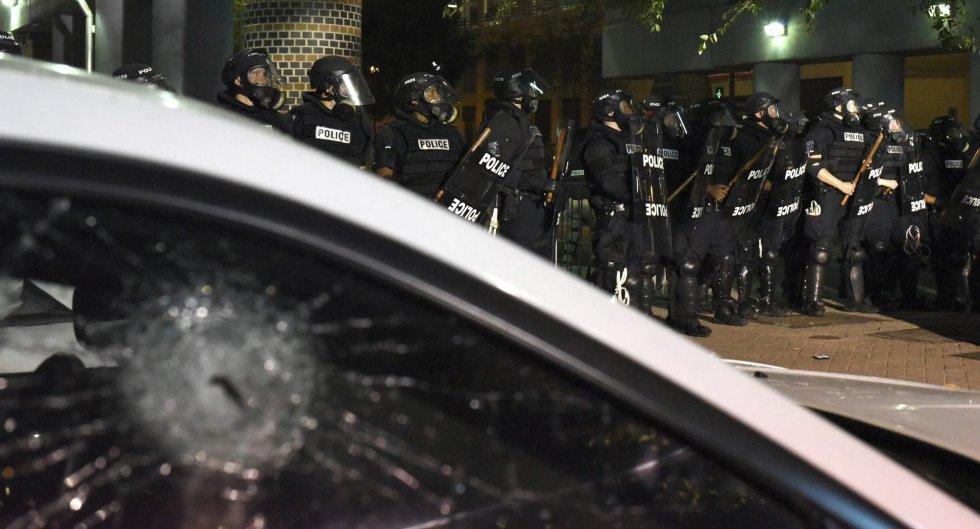 Policías antidisturbios permanecen en guardia junto a un coche con la ventanilla rota durante unos disturbios en Charlotte en Carolina del Norte (Estados Unidos).