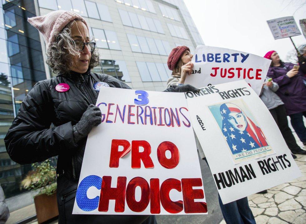 Dos activistas muestran pancartas contra las políticas estadunidenses.