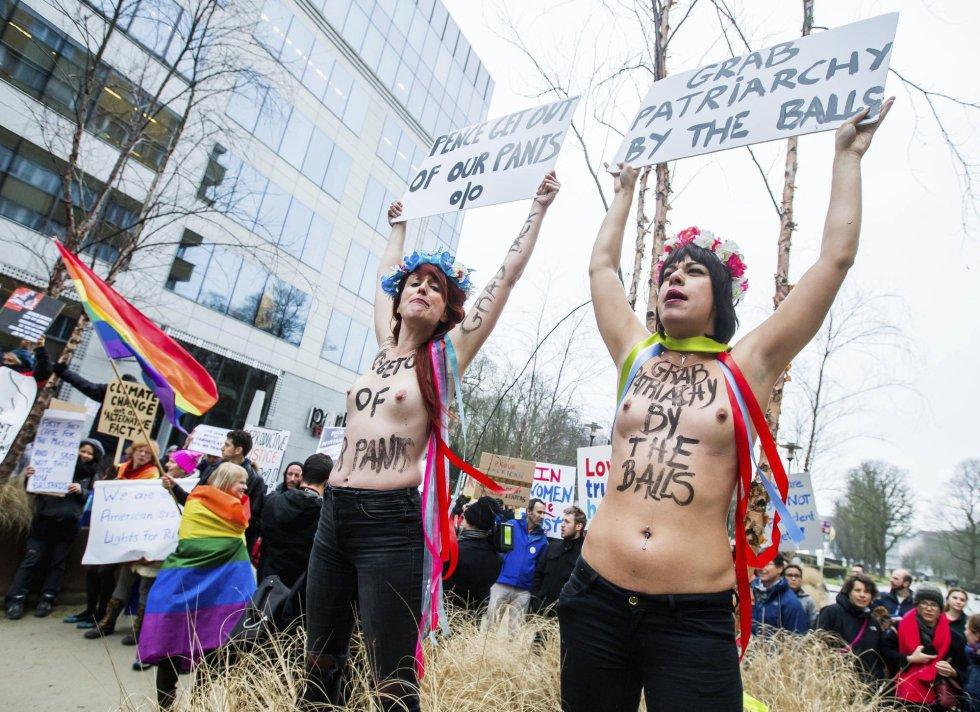 Varias activistas del movimiento feminista FEMEN muestran pancartas contra las políticas estadunidenses.
