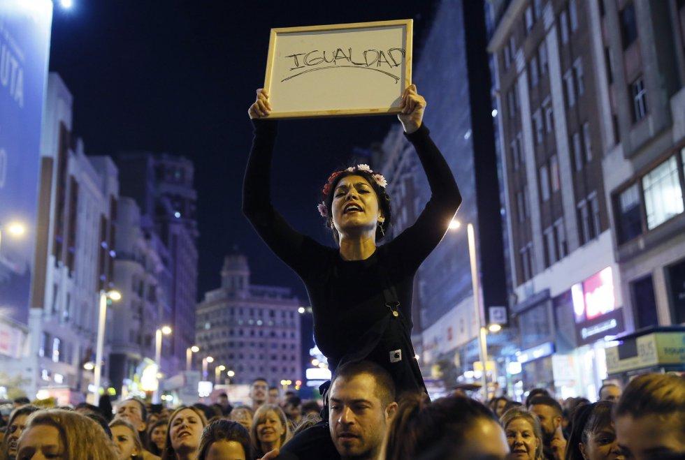 Una de las mujeres de la marcha sostiene una pizarra pidiendo igualdad