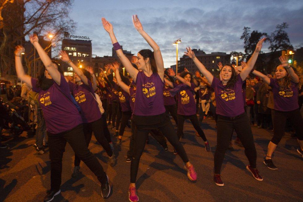 Varias mujeres con camisetas moradas bailan en la protesta de Barcelona