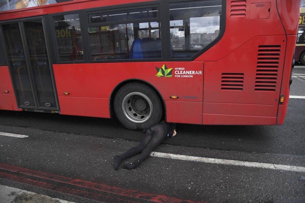 Una mujer yace bajo un autobús.