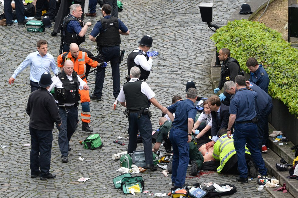 El parlamentario conservador Tobias Ellwood (en el centro, con traje) trata de salvar la vida al policía acuchillado por el atacante.