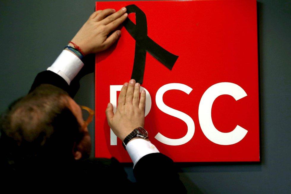 Un militante coloca un crespón negro en el logo del PSC de la sede en Barcelona tras conocerse el repentino fallecimiento de la socialista Carme Chacón.