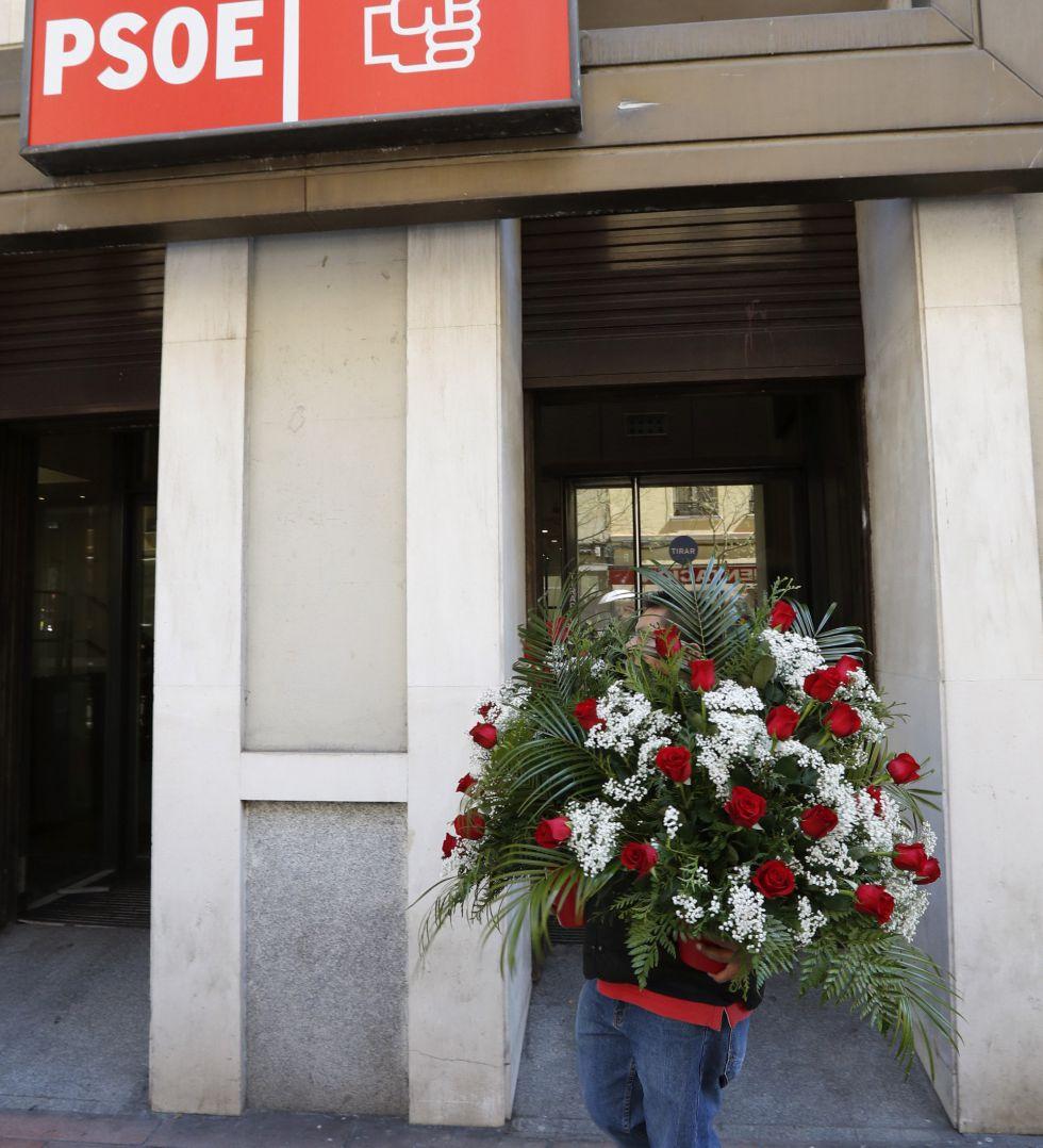 Un operario lleva una corona de flores a la sede del PSOE en la calle Ferraz.