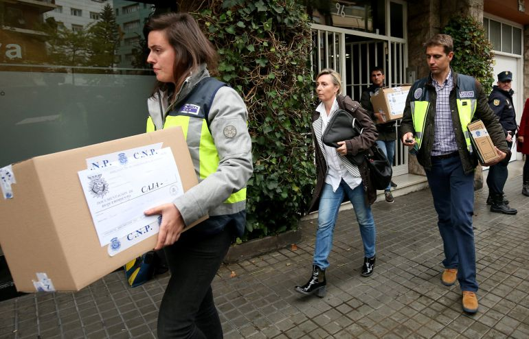 Police investigators carry boxes of evidence from the residence of former Catalonian regional president Jordi Pujol after a high court judge jailed his son Jordi Pujol Ferrusola