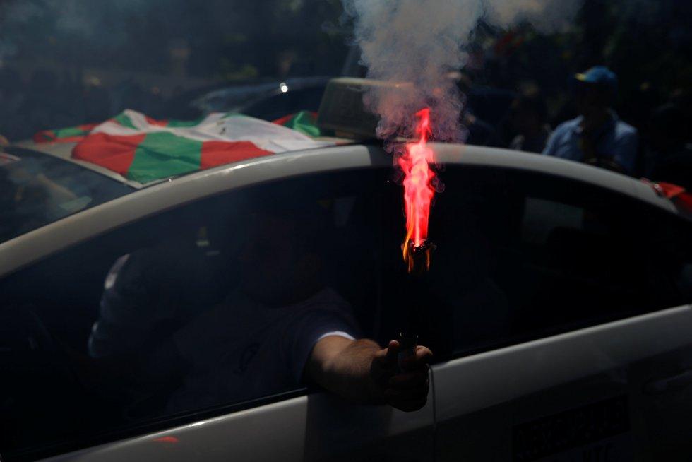 Uno de los taxistas enciende una llamarada durante la manifestación en Madrid