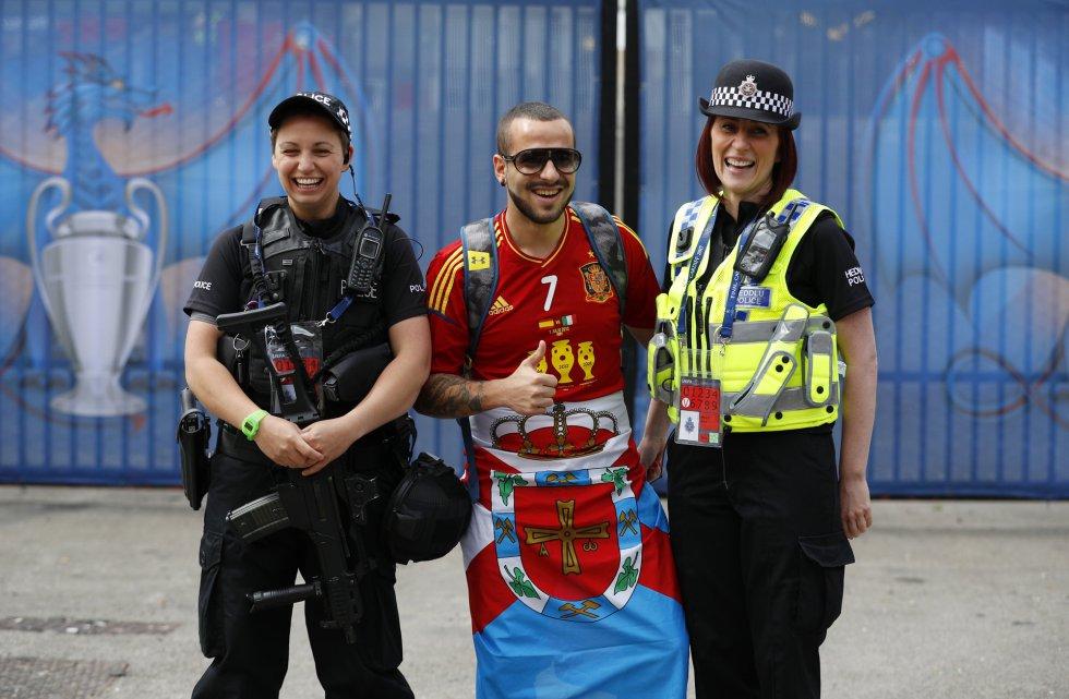 Un aficionado español posa con los miembros de seguridad desplazados ya al Millennium Stadium de Gales.