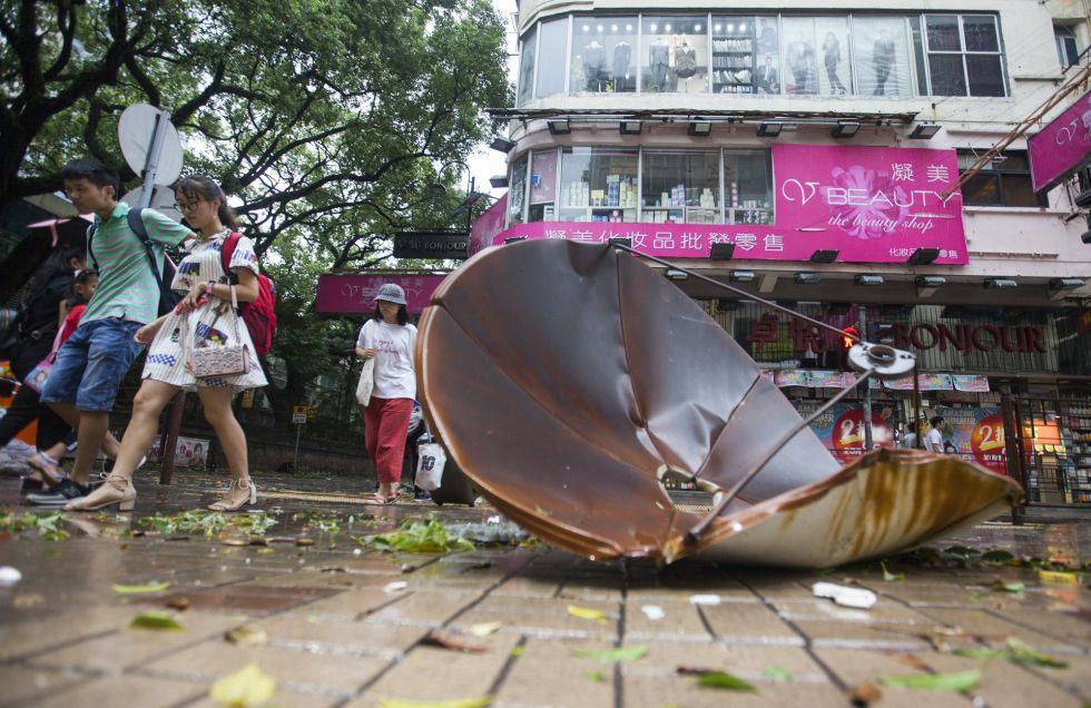 Varios viandantes pasan junto a un plato de un satélite que voló de un tejado por el paso del tifón 'Hato' en Hong Kong (China).