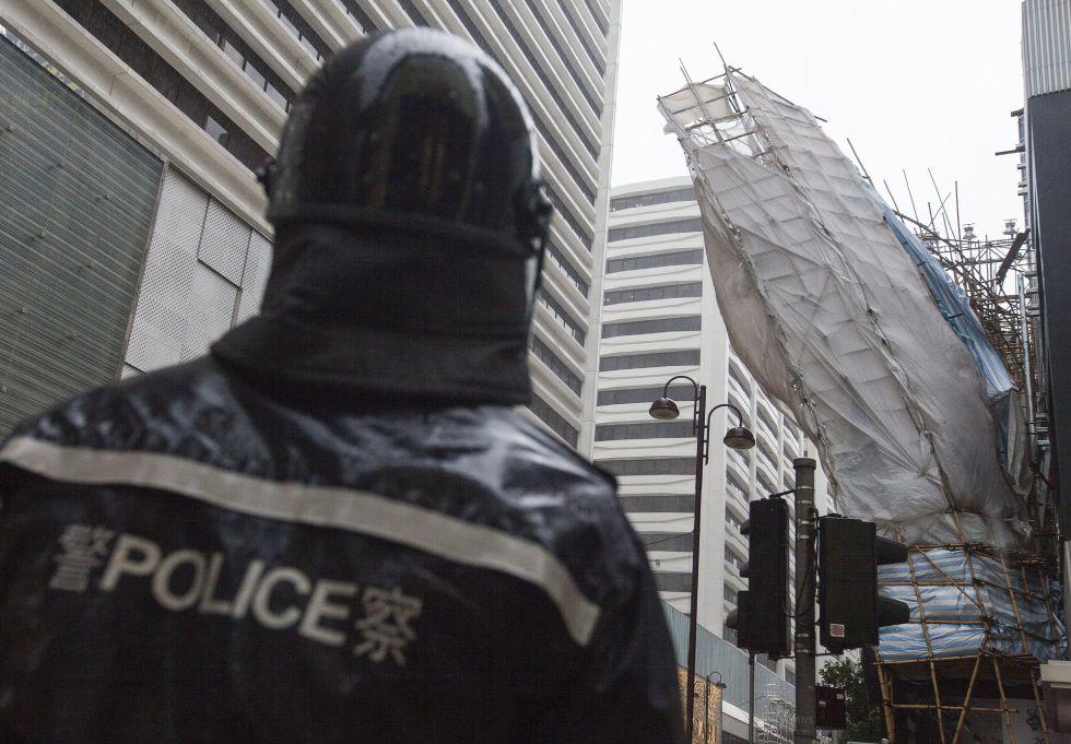 Un policía vigila un andamio desprendido parcialmente de una fachada en un lugar en construcción por el paso del tifón 'Hato' en Hong Kong (China).