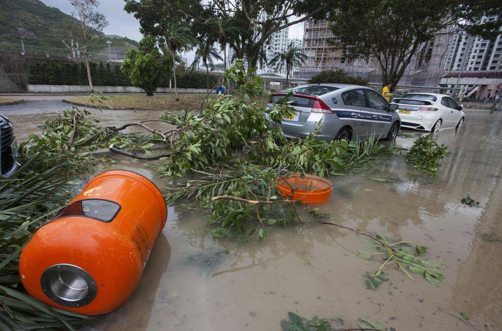 Vista de varios coches, papeleras y ramas caídas en una zona inundada durante el paso del tifón 'Hato' en Hong Kong (China).