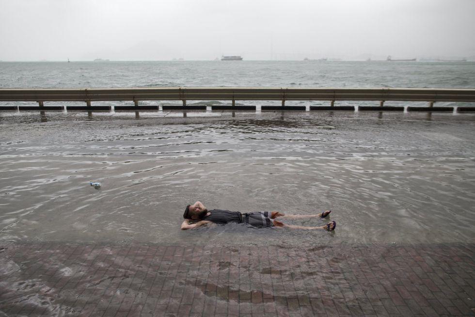 Mark Mooney, británico residente en Hong Kong, descansa en una calle inundada por el paso del tifón 'Hato' en Hong Kong (China).