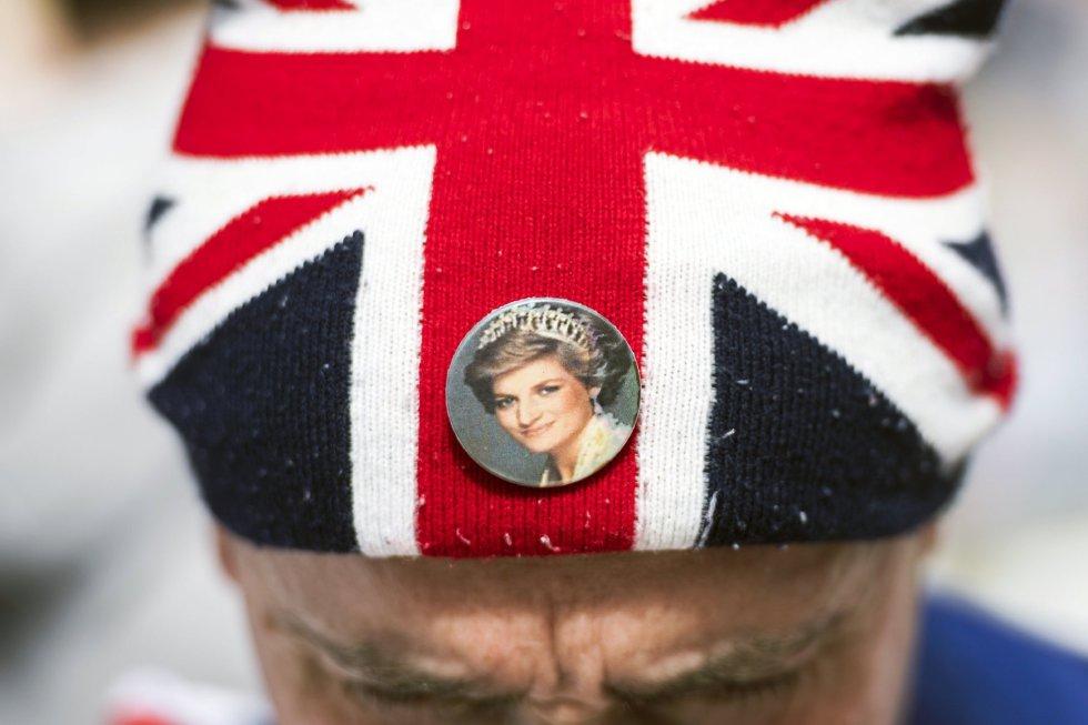 Un hombre porta un tributo en memoria de la princesa Diana de Gales a las puertas del Palacio de Kensington en Londres.