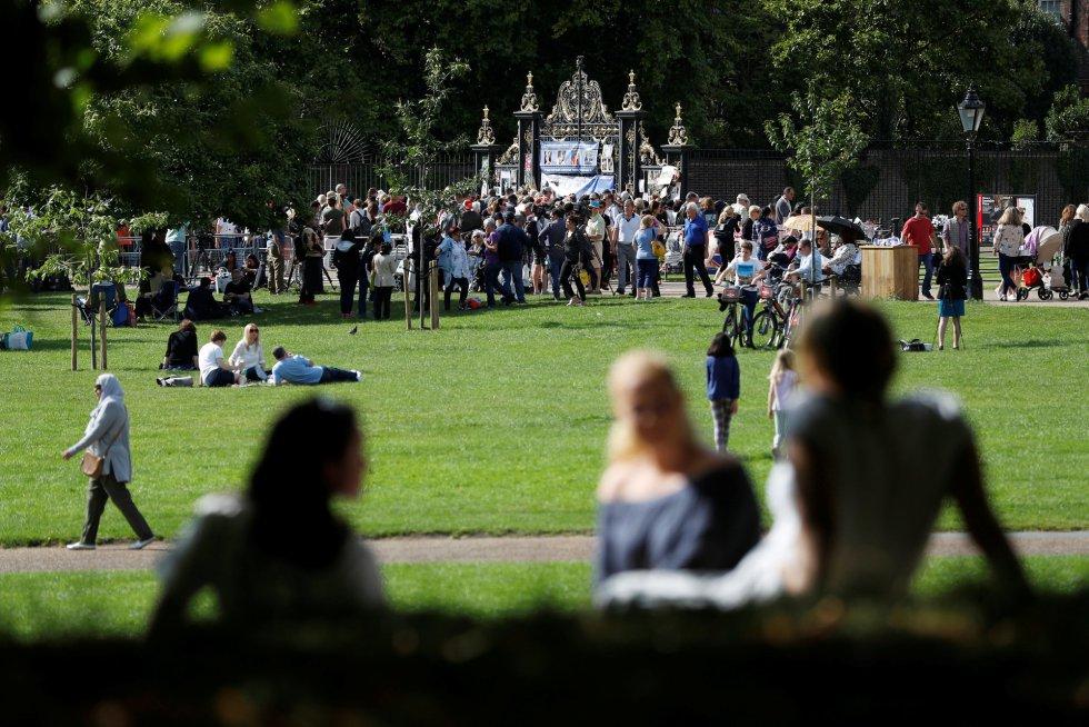Gente sentada en el suelo en los exteriores del palacio de Kensington.