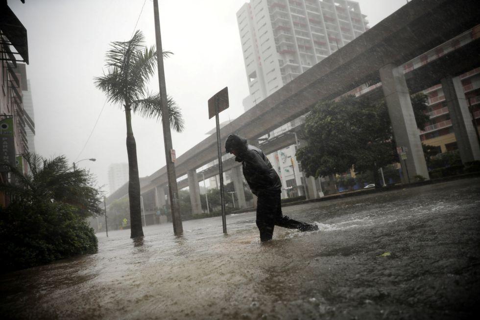 Una persona cruza una calle inundada en Miami, Florida (EEUU).