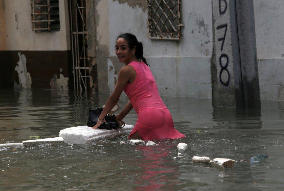 Una mujer utiliza una plancha para mantener secos sus zapatos mientras cruza una calle inundada en La Habana.
