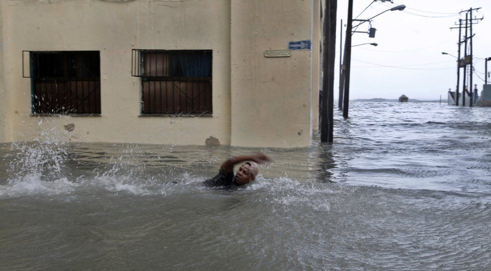 Un hombre nada por una calle inundada de la capital cubana.
