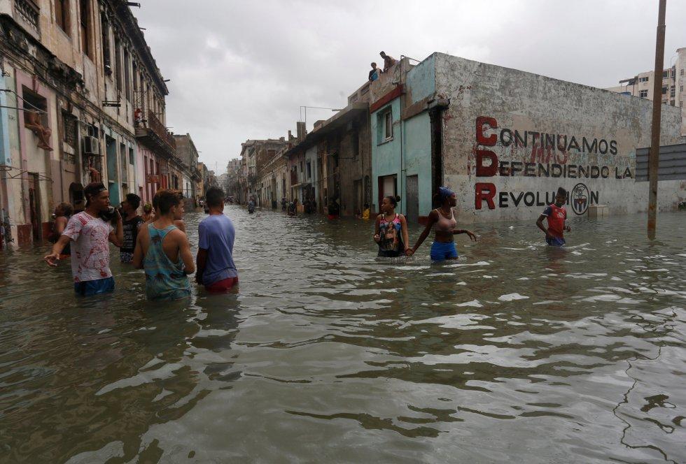 Ciudadanos de La Habana se abren paso en una calle inundada.