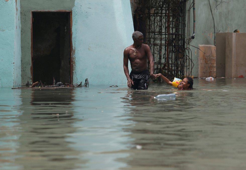 Un hombre sujeta a una niña con un flotador en una calle inundada de La Habana.