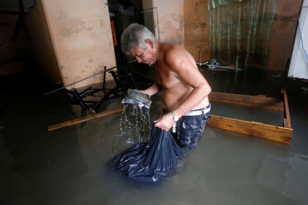 Un hombre comprueba el estado de sus pertenencias tras el paso del huracán.