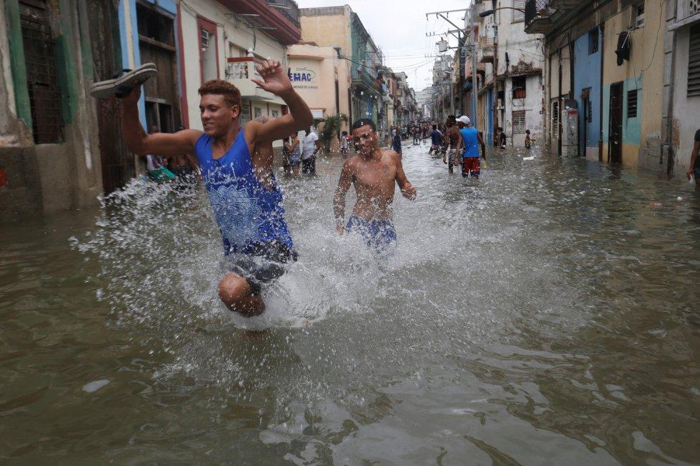Jóvenes corriendo a través de una de las calles inundadas en la Habana tras el paso del huracán Irma.