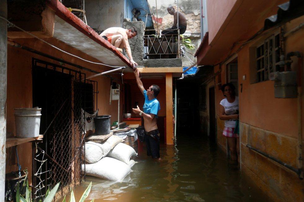 Un hombre le pasa bebidas a un vecino encaramado a un tejado.