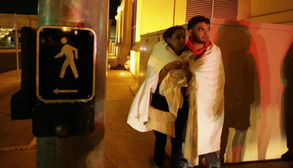 Varias personas permanecen a la entrada del hotel Mandalay Bay.