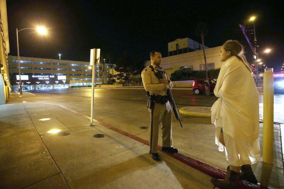 Un agente de policía permanece en guardia junto a una mujer envuelta en una manta.