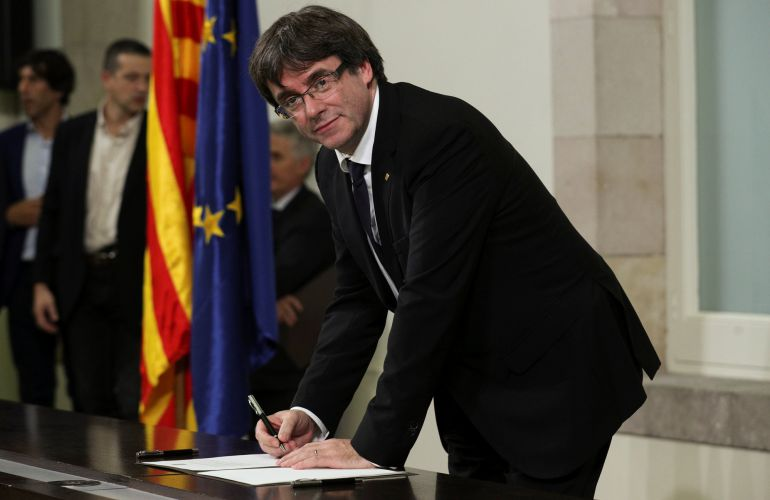 Catalan President Carles Puigdemont signs a declaration of independence