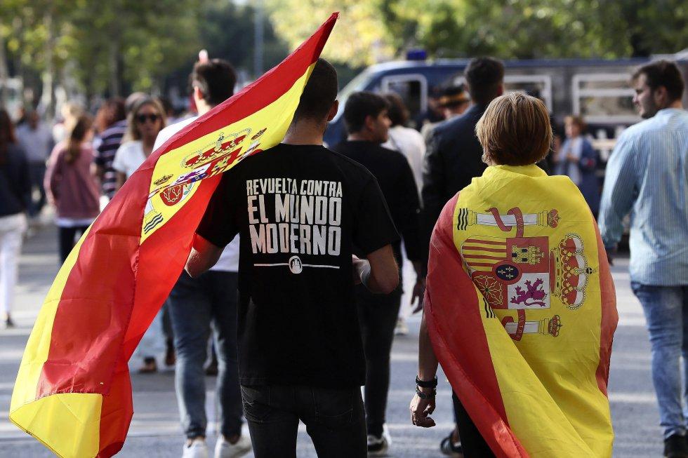 Dos personas portan la bandera española antes del inicio del desfile del Día de la Fiesta Nacional.