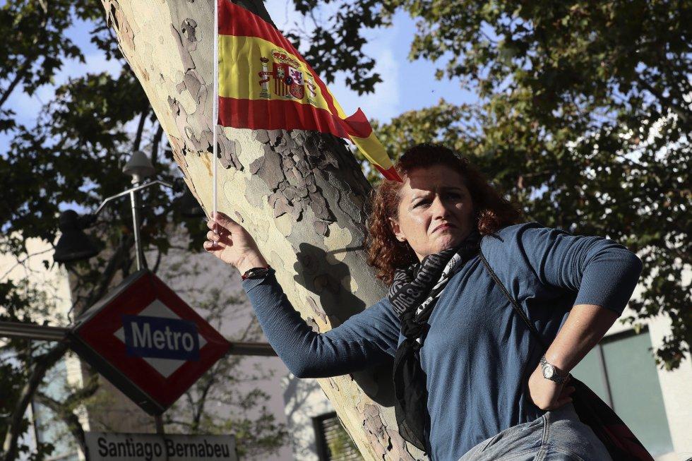 Una mujer porta una bandera española antes del inicio del desfile del Día de la Fiesta Nacional, al que asiste el Gobierno en pleno y la mayoría de líderes políticos.