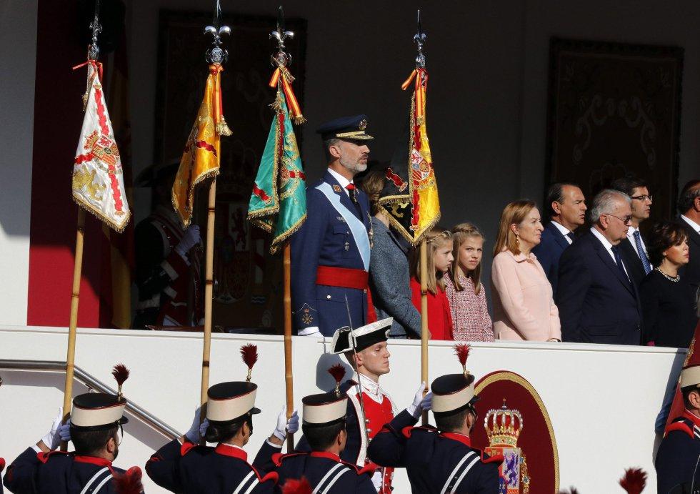 Los Reyes junto a sus hijas, la princesa Leonor y la infanta Sofía, presiden el desfile del Día de la Fiesta Nacional, al que asiste el Gobierno en pleno y la mayoría de líderes políticos.