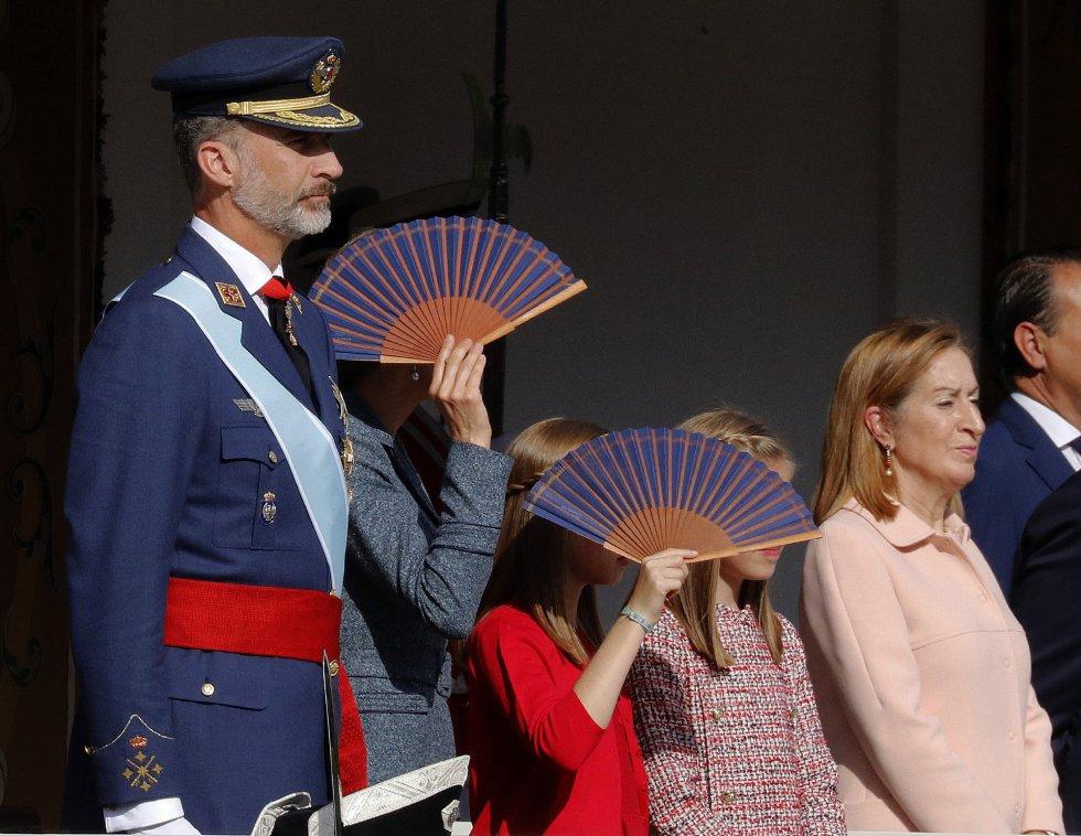 La reina Letizia y sus hijas, la princesa Leonor y la infanta Sofía, se protegen del sol con unos abanicos, junto al Felipe VI, y la presidenta del Congreso, Ana Pastor, durante el desfile del Día de la Fiesta Nacional que presiden los Reyes y al que asiste el Gobierno en pleno y la mayoría de líderes políticos.