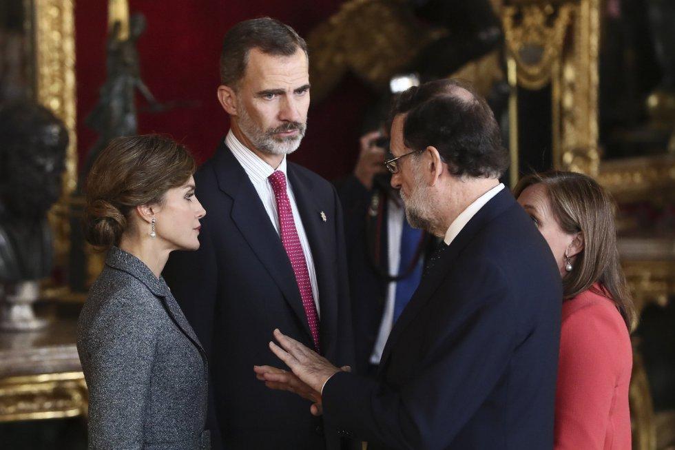 Los Reyes conversan con el presidente del Gobierno, Mariano Rajoy, acompañado de su mujer Elvira Fernández a su llegada a la tradicional recepción ofrecida hoy en el Palacio Real con motivo del Día de la Fiesta Nacional.