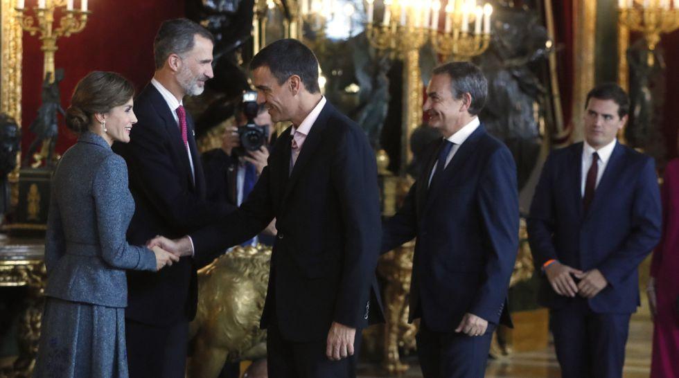 Los Reyes saludan al secretario general del PSOE, Pedro Sánchez (3i) y el expresidente del Gobierno José Luis Rodríguez Zapatero, a su llegada a la tradicional recepción ofrecida hoy en el Palacio Real con motivo del Día de la Fiesta Nacional.