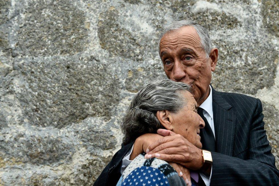 El presidente luso, Marcelo Rebelo de Sousa, besa a una mujer mientras llora, durante una visita a los municipios del centro del país afectados por los incendios forestales