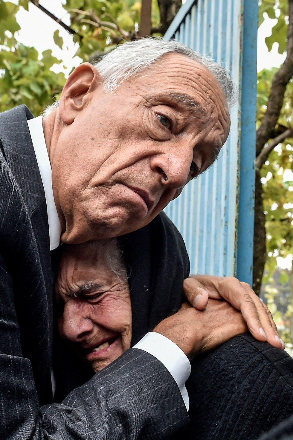 El presidente luso, Marcelo Rebelo de Sousa, abraza a una mujer mientras llora, durante una visita a los municipios del centro del país afectados por los incendios forestales