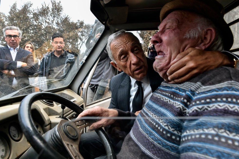 El presidente luso, Marcelo Rebelo de Sousa, consuela a un hombre mientras llora, durante una visita a los municipios del centro del país afectados por los incendios forestales