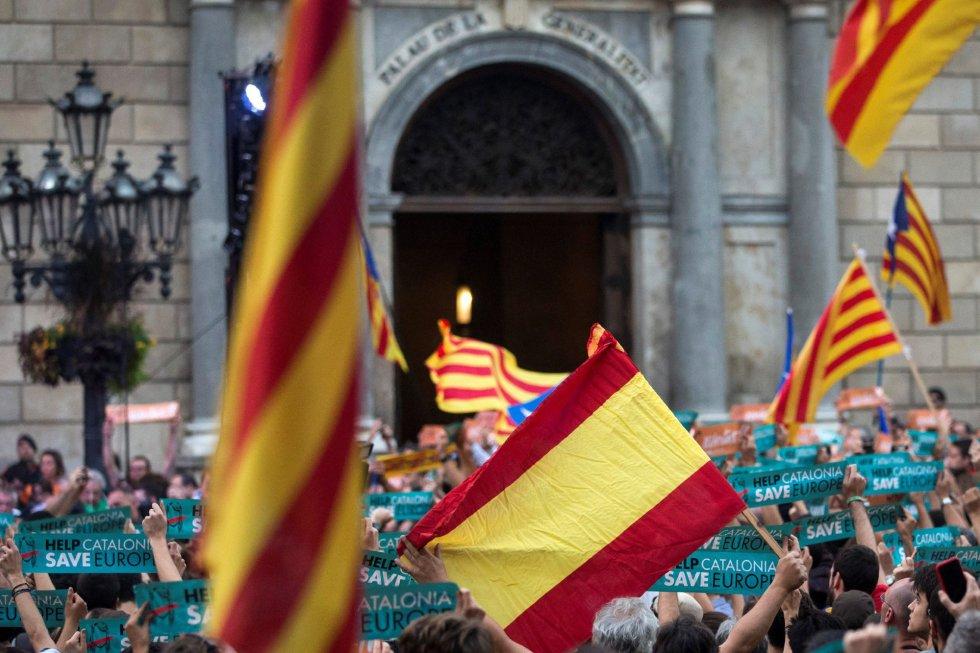 Una bandera española se mezcla con independentistas concentrados esta tarde en la Plaza Sant Jaume de Barcelona, ante el Palau de la Generalitat, sede del gobierno catalán, para festejar que el Parlament ha declarado de forma unilateral la independencia de Cataluña.