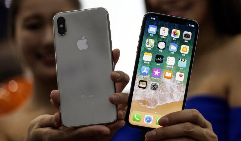 170b181ac7e Dos mujeres sostienen dos ejemplares del nuevo iPhone X en una tienda de  Apple en Taipei
