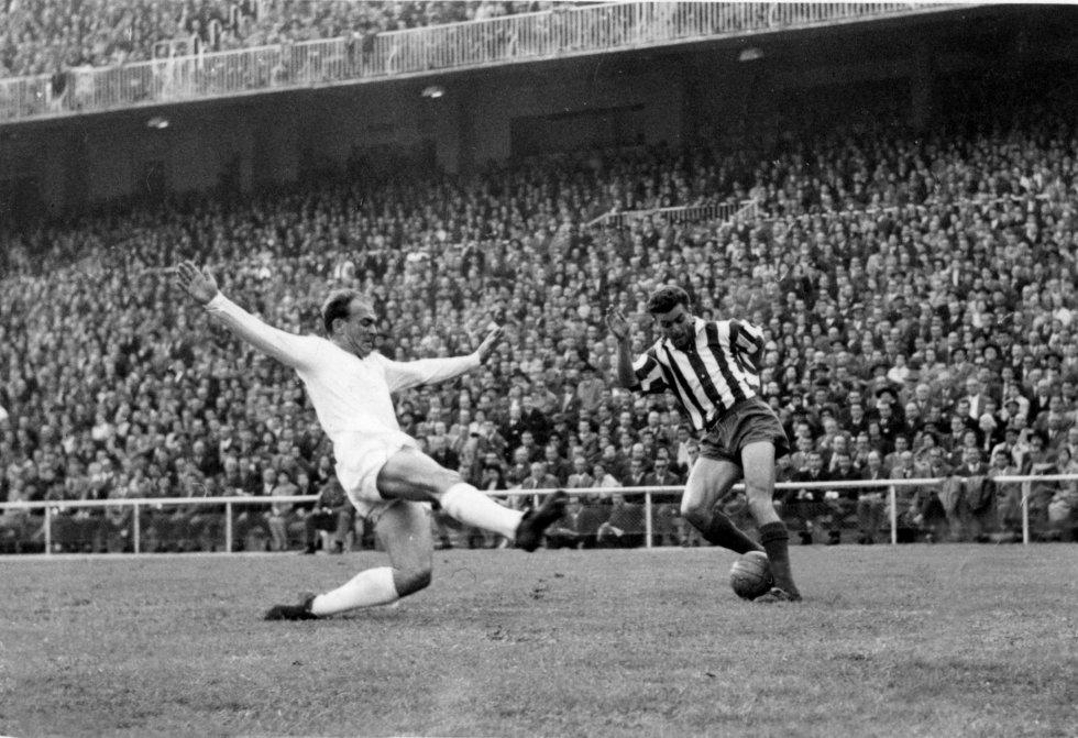 Alfredo Di Stefano, (i) bloquea al jugador del Atlético de Madrid, Miguel, durante el partido correspondiente a la octava jornada de Liga, celebrado en el estadio Santiago Bernabéu, que finalizó con el resultado de 5-0.