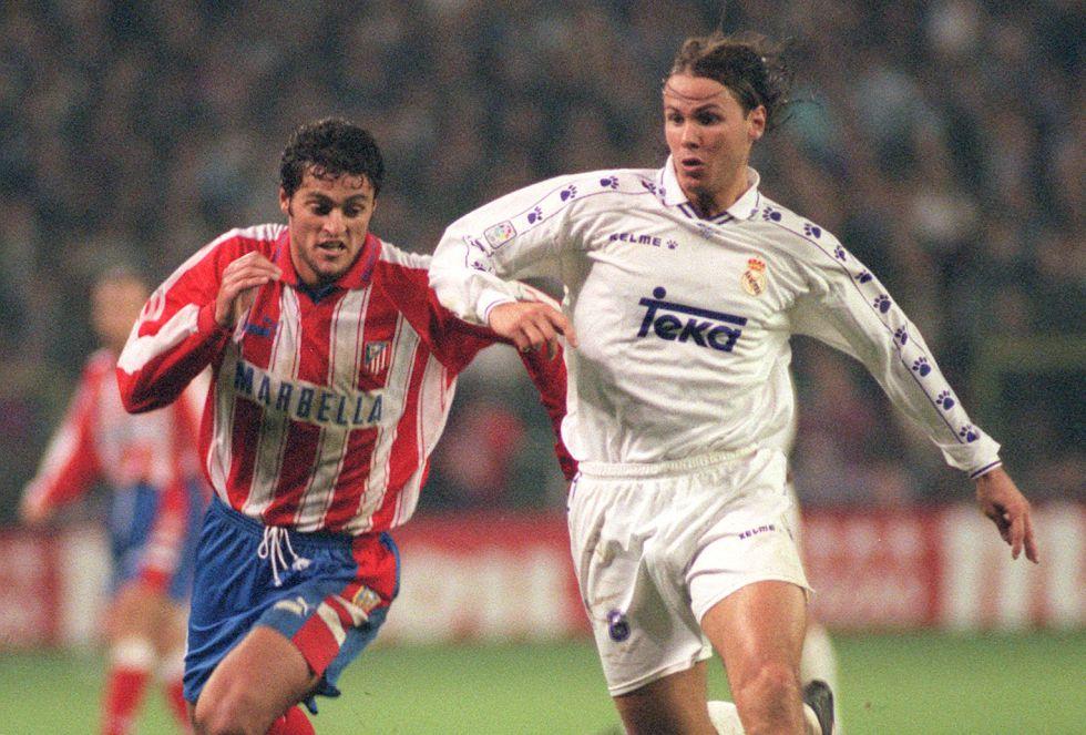 El jugador del Real Madrid Redondo intenta eludir a Kiko del Atlético de Madrid, durante el encuentro disputado hoy y que finalizó con la victoria del equipo blanco por 1-0.