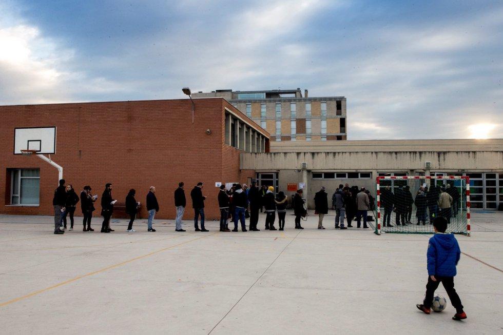Varias personas esperan la apertura del colegio Lluis Piquer en Parets del Vallés, más de cinco millones y medio de catalanes están llamados a las urnas en esta jornada de elecciones autonómicas del 21D.