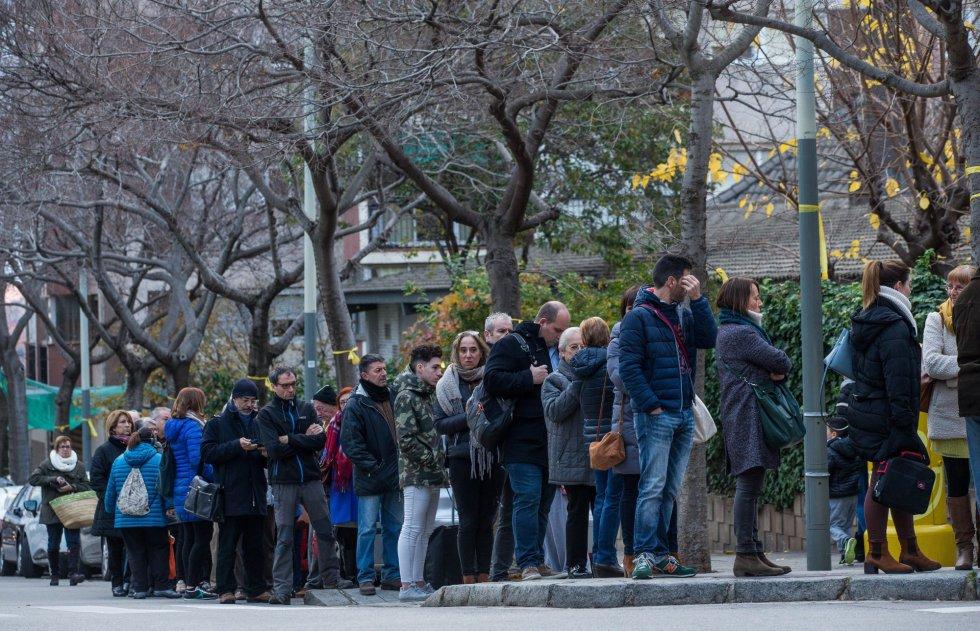Una fila de ciudadanos esperan para votar en el exterior del colegio electoral Narcís Monturió de Barcelona, más de cinco millones y medio de catalanes están llamados a las urnas en esta jornada de elecciones autonómicas.