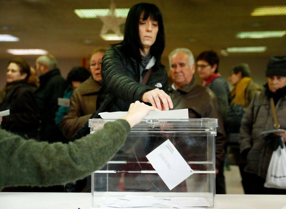Una mujer deposita el voto en una urna.
