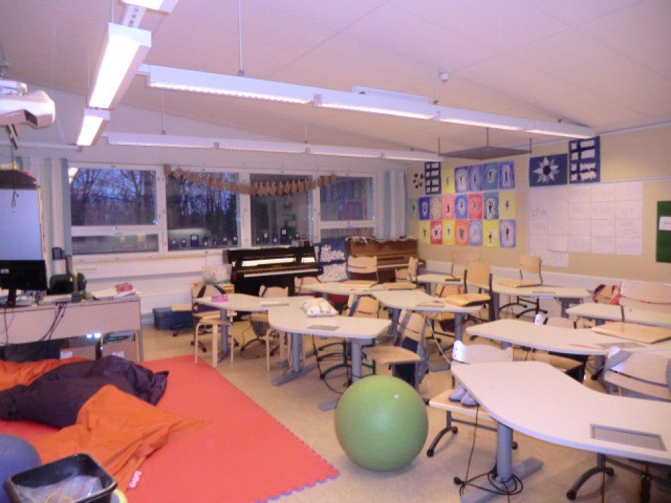 Aula con mesas ergonómicas y una zona para sentarse en el suelo.