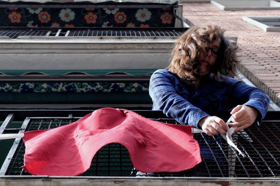 Una mujer se dispone a colgar un delantal en el balcón de su casa de Valladolid para apoyar a las mujeres que hacen huelga.
