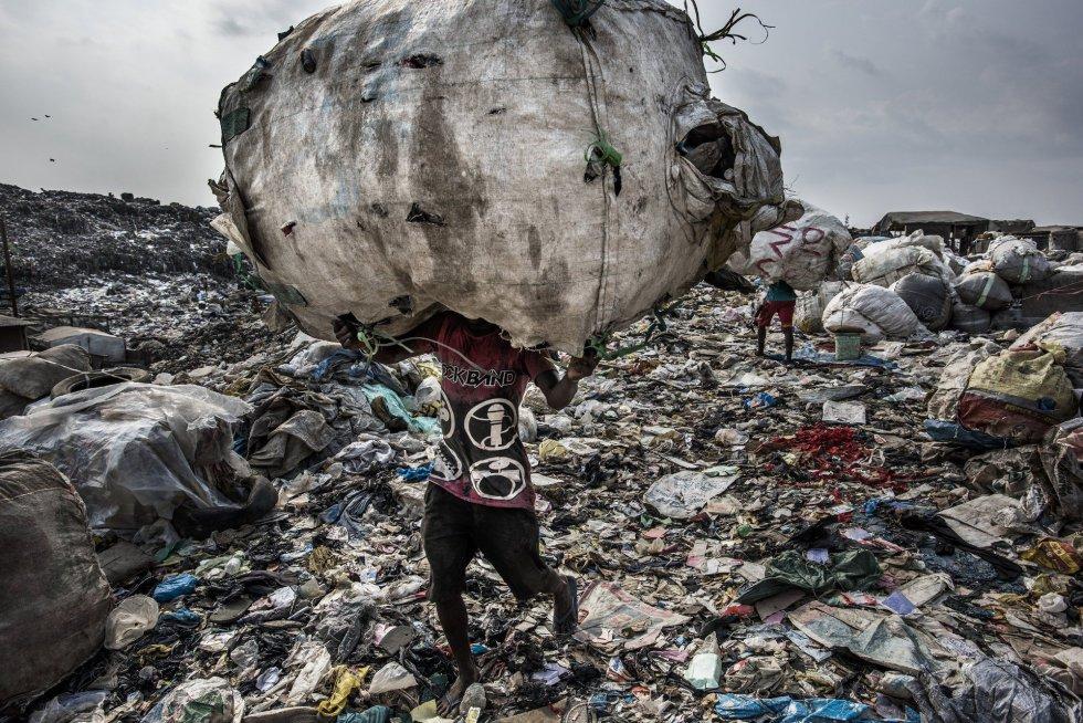 Imagen captada por el fotógrafo Kadir van Lohuizen, ganador del primer premio de la categoría 'Environment - Stories'. La foto muestra a un hombre mientras carga un enorme lomo de botellas recogidas para su reciclaje en el vertedero de Olusosun en Lagos, Nigeria, el 21 de enero de 2017.